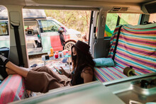 High Angle Side View Of Female Hipster Sitting In Van And Browsing Smartphone During Trip In Summer