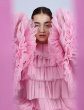 Eccentric Young Female Model Wearing Fluffy Pink Tulle Gown With Ruffles Seen Through Round Hole Looking At Camera
