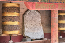 Piece Of Stone With Image Of Buddha Engraved On Surface Between Tibetan Rolls And Red Shabby Columns