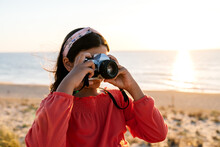 Anonymous Stylish Teen Girl In Casual Clothes Standing On Sandy Beach And Taking Photo Of Sunset Over Ocean