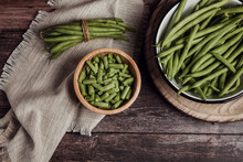 Top View Of Fresh Whole And Cut Green Beans In Wooden And Metal Bowls On Linen Towel