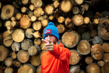 Unrecognizable Young Guy In Warm Hat And Outwear Pointing At Camera With Index Finger While Standing Near Stack Of Cut Tree Trunks In Woods