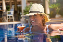 Attractive Relaxed Young Female In Straw Hat Chilling In Outdoor Swimming Pool And Enjoying Cocktail Drink During Summer Holidays In Tropical Resort