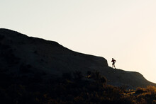 Side View Silhouette Of Unrecognizable Athlete Running Up On Mountain Slope During Workout At Sunset