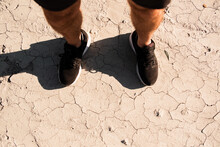 From Above Of Crop Faceless Male Athlete In Stylish Black Sneakers And Shorts Standing On Arid Ground  After Training In Countryside