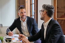 Adult Male Managers In Formal Clothes Sitting At Table With Diagrams And Discussing Results Of Marketing Company During Meeting In Workspace
