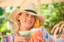 Unrecognizable Young Stylish Female Traveler In Swimwear And Straw Hat Drinking Refreshing Smoothie While Relaxing On Sunbed On Beach