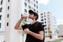 Low Angle Of Male In Respiratory Mask And Black Wear Drinking Water From Bottle Near Buildings And Looking Away