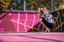Ground Level Side View Of Young Stylish Female In Ornamental Clothes Squatting On Bright Sports Ground Near Grid Fence And Looking At Camera