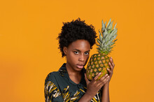 Serious Young Black Female Looking At Camera Holding Pineapple In Stylish Apparel On Orange Background