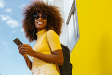 Black Woman With Afro Hair Listening To Music On Mobile In Front Of A Yellow Wall