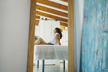 Side View Serene Adult Female In Casual Summer Wear Resting With Legs Crossed On Table On Sunny Terrace And Reflecting In Mirror