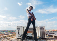 From Below Full Body Slim Attractive African American Female Model Standing Confidently On Rooftop In Urban Environment And Looking At Camera