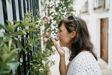 Side View Smiling Adult Female Wearing Casual Summer Shirt Smelling Fragrant White Flowers Growing Near Window Bars On Narrow Sunny Street