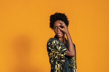 Young Contemplative African American Female In Trendy Wear With Afro Hairstyle Standing With Raised Arm Showing Eye Gesture While Looking Away