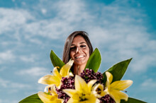 From Below Of Young Content Female In Trendy Yellow Apparel Standing With Raised Arm Holding Lily Bouquet Under Blue Cloudy Sky And Looking At Camera
