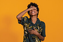 Young Happy African American Female In Trendy Wear With Afro Hairstyle Standing Covering Eyes Standing On Studio With Orange Background