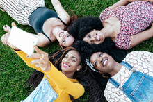 From Above Of Diverse Multiracial Women Lying On Grass In Park And Taking Photo On Selfie Camera Of Smartphone While Having Fun At Weekend