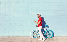 Side View Of Unrecognizable Young Guy In Casual Outfit Using Mobile Phone While Standing Near Stylish Bicycle And Blue Wall On City Street