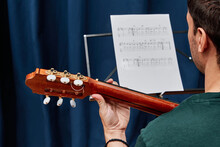Cropped Back View Of Unrecognizable Focused Male Guitarist Playing Acoustic Guitar With Music Sheet