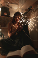 Serene Female In Domestic Wear Sitting In Cozy Room In Evening With Illuminated Vintage Lantern While Chilling At Home And Looking Away