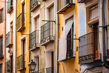 Low Angle Of Aged Apartment Building With Colorful Painted Facade And Small Balconies With Metal Railings On Street Of Cuenca Town In Spain