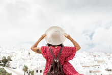 Back View Of Anonymous Stylish Tourist With Straw Hat And Raised Arms Contemplating Old Houses In Rhodes Under Cloudy Sky