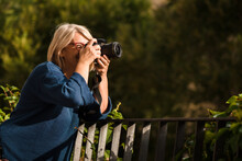 Side View Of Serious Adult Blond Female Photographer With Professional Photo Camera Leaning On Fence And Looking Away While Standing Against Green Bushes And Taking Pictures Of Nature
