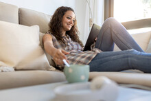 Positive Female Wearing Domestic Clothes Sitting On Soft Couch At Home And Chatting On Social Media With Friends Via Tablet