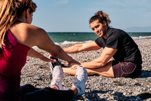 Fit Couple Sitting On Beach And Doing Forward Bends While Stretching Legs And Warming Up Before Workout In Summer