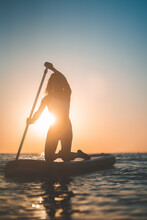 Unrecognizable Silhouette Of Woman In Swimsuit On SUP Board In Calm Sea At Sunset In Summer