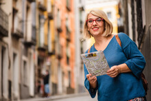 Low Angle Of Female Traveler Holding Touristic Map And Checking Route While Standing On Narrow Paved Street With Old Buildings In Cuenca Town In Spain