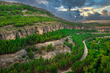 From Above Of Spectacular Landscape With Curved Roadway Running On Slope Of Rocky Mountain Covered With Green Trees Under Cloudy Sky