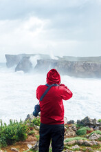 Back View Of Anonymous Traveler In Raincoat Taking Picture Of Stormy Sea Waving On Rocky Cliff On Cloudy Day In Bufones De Llames Pría In Spain