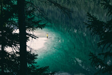 From Above Of Anonymous Traveler Admiring View Of Tranquil Lake With Bright Water Surrounded By Green Forest In Italy