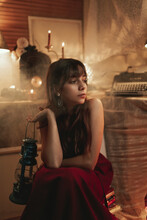 Peaceful Female In Red Dress Sitting In Cozy Room With Old Fashioned Kerosene Lantern While Enjoying Evening And Looking Away