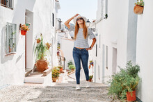 Happy Charming Female Tourist Wearing Stylish Sunhat Standing On Historic Street During Stroll In Frigiliana And Looking Up During Vacation
