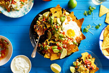 Chilaquiles - Mexican Breakfast Made Of Black Beans, Corn, Tortilla Chips And Fried Eggs On Blue Wooden Table