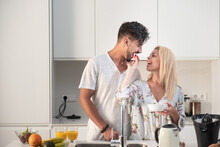 Tender Couple Eating Strawberries And Drinking Fresh Orange Juice While Hugging In Kitchen In Morning During Breakfast