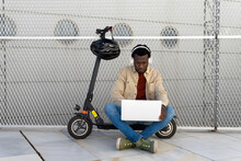 Black Male Sitting On Parked Electric Scooter On Street And Messaging On Social Media Via Netbook While Listening To Music In Headphones And Enjoying Weekend