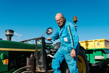 Low Angle Of Senior Workman In Blue Uniform Standing Near Farm Vehicle And Looking Down In Sunlight