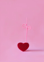 Red Vivid Heart With Curved Straw Placed On Pink Background In Modern Studio