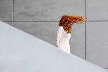 Side View Of Unrecognizable Female With Long Red Hair Fluttering In Wind Standing Against Gray Concrete Wall On Street