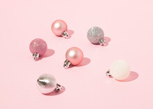 From Above Of Decorative Christmas Baubles Arranged On Pink Background In Studio For Holiday Celebration