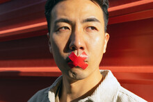 Crop Pensive Asian Male With Red Adhesive Tape On Lips Standing Against Red Metal Fence And Looking Away Thoughtfully