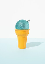 Glittering Blue Christmas Bauble Placed In Decorative Waffle Cup From Ice Cream On Table In Studio On Blue Background