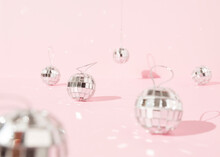 Shiny Christmas Baubles In Shape Of Disco Balls Placed On Pink Background In Studio