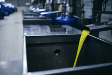 Closeup Of Yellow Chemical Liquid Flowing From Metal Tap In Industrial Area Of Modern Plant