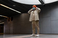 Full Body Focused Stylist Asian Male Wearing Casual Outfit And Face Mask Standing On Concrete Building Hallway Looking Away