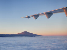 White Wing Of Modern Aircraft Flying Over Fluffy Clouds At Sunrise On Background Of Mountain Top In Morning